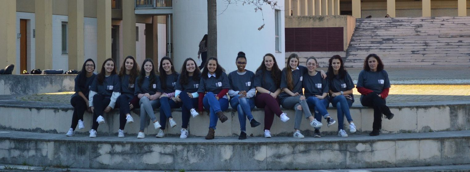 Grupo de estudantes do 2.º ano da licenciatura em Educação e Formação, vestidas com a t-shirt do Instituto de Educação, sentadas nas escadas que dão acesso ao lago. Atrás, vista do edifício.
